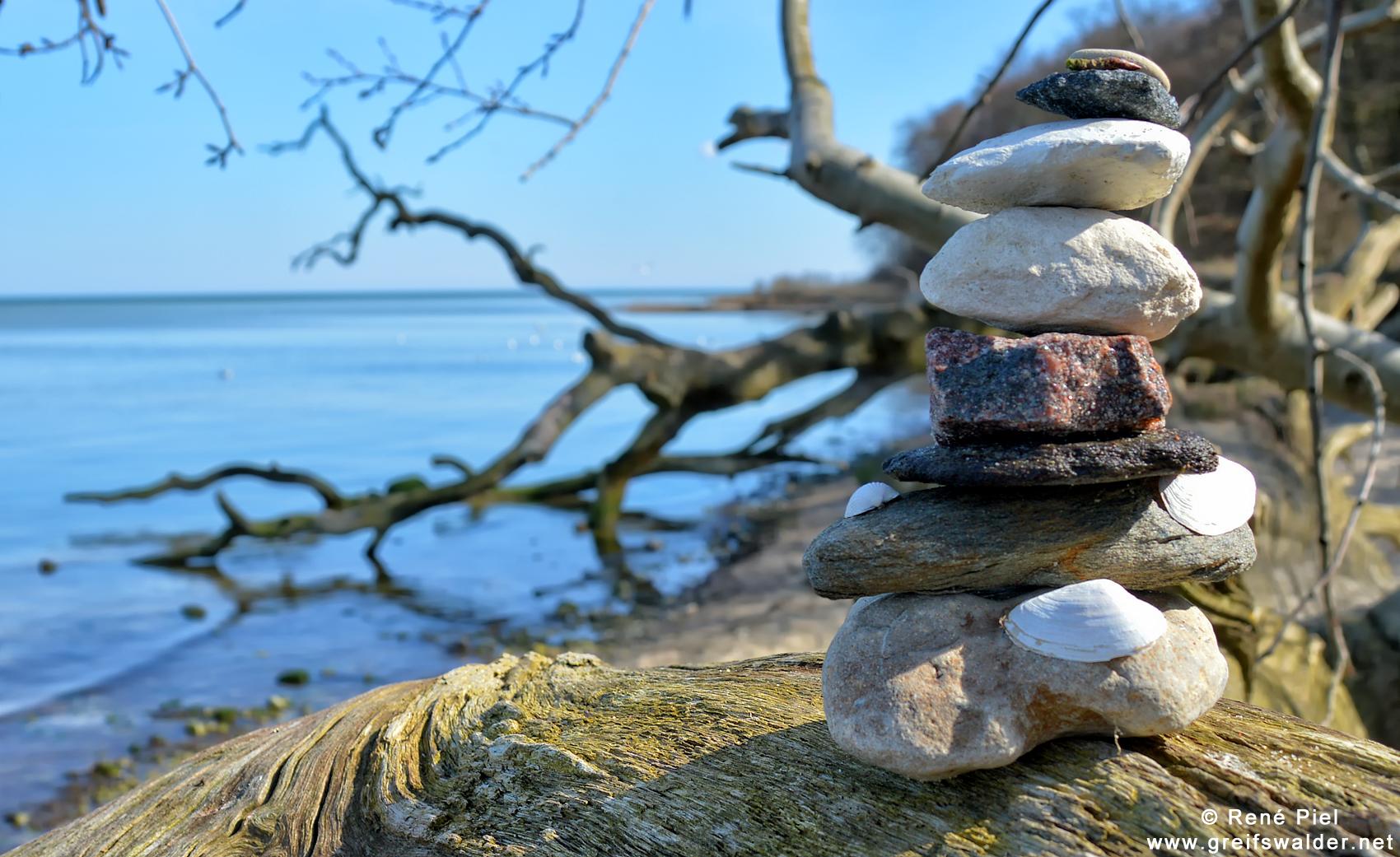 Stein auf Stein auf Baum am Strand